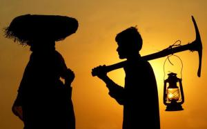 Indian labourers are silhouetted against sunset at construction site in Chandigarh