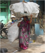 Member of female waste pickers group carrying almost 15 kg of waste sacks on the streets of Gomtipur in Ahmedabad in May 2013