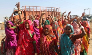 Women shout slogans before boycotting an environmental public hearing for proposed nuclear power plant at Nava Gam, Bhavnagar