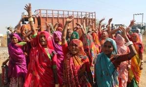 Women shout slogans before boycotting an environmental public hearing for proposed nuclear power plant at Nava Gam, Bhavnagar