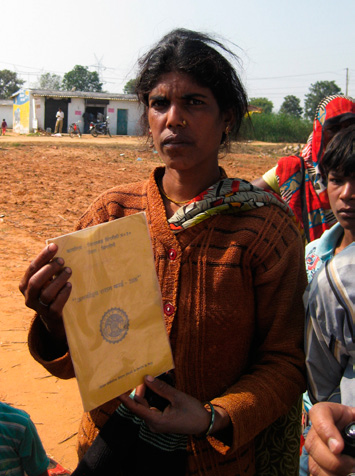Relocated woman holds up relocation card