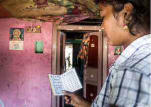 Former spinning mill worker looking at a cashbook. She had to quit her job due to health problems. Her family had to borrow money at high interest rates. Without a job she can no longer contribute to paying off the loan which maker her very worried