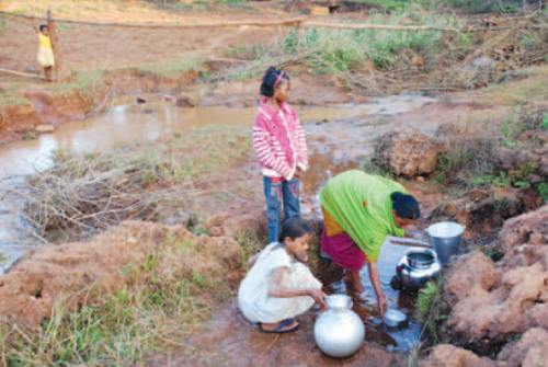 Children help  mother in collecting contaminated water from a stream near Tholkobad village