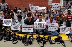 Kashmiri journalists sit during a protest in Srinagar, India, Thursday, Aug. 25, 2011. The protest was against alleged recent attacks and harassment of journalists by the Jammu Kashmir police in Srinagar. (AP Photo/Mukhtar Khan)
