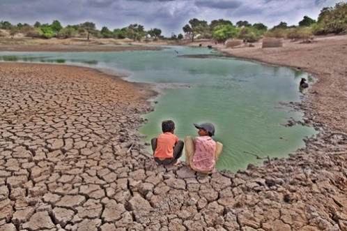Children wash their hands in a partially dried-out natural pond at Badarganj village, in Gujarat
