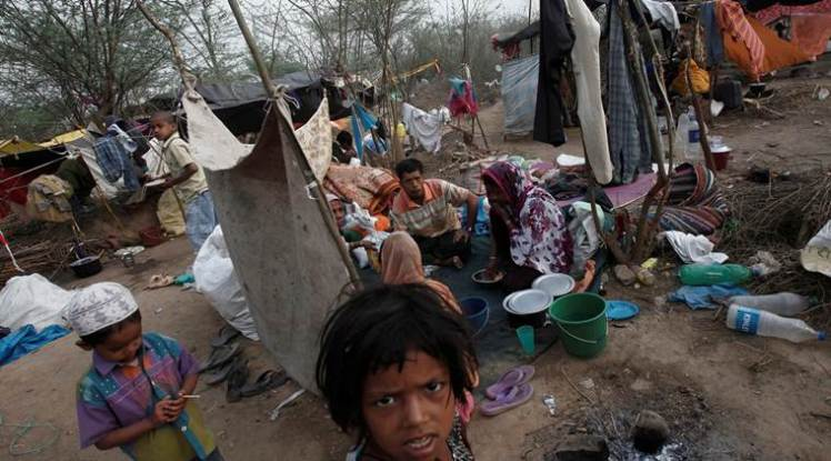 FILE PHOTO - A family, who says they belong to the Burmese Rohingya Community from Myanmar, eat their breakfast at a makeshift shelter in a camp in New Delhi