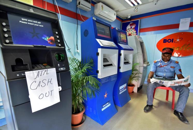 A security guard reads a newspaper inside an ATM counter as a notice is displayed on an ATM in Guwahati
