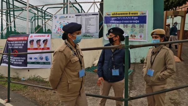 Police officers wearing protective face masks stand outside Himachal Pradesh Cricket Association Stadium before the start of the first One-day International cricket match between India and South Africa, amid coronavirus fears, in Dharamsala